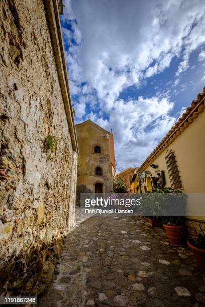 narrow alley and old houses with plants outside in castelmola taormina sicily italy - finn bjurvoll ストックフォトと画像