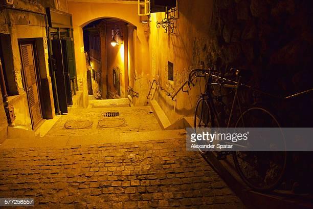 narrow alley at night in sibiu, romania - sibiu stock-fotos und bilder