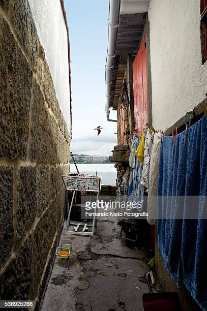 narrow alley with clothes hanging in a fishing village. - callejon stock pictures, royalty-free photos & images
