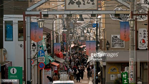 a narrow alleyway leads off into the distance of tokyo japan. the street is populated with shoppers and lined with shops and laterns and signs. overhead cables run the length of the street. - ショッピングエリア ストックフォトと画像