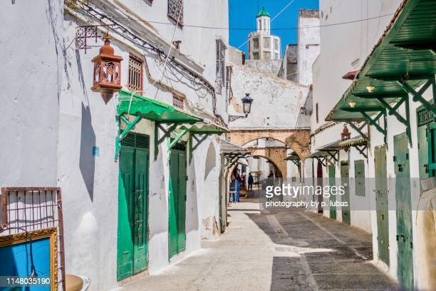 narrow alleyways weave their way through the old town (medina) of tetouan - tetouan stock photos and pictures
