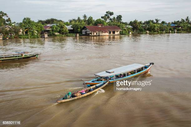 Narrow boat being pulled along a river in Borneo
