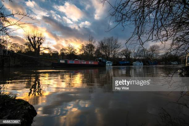 Narrow boat glides slowly by as the sun sets on the horizon near Leyton in London on the River Lee.