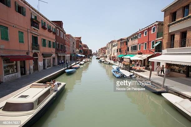 CONTENT] Narrow canal in Burano with boats moored and colored Italian buildings on sides July 16 2013