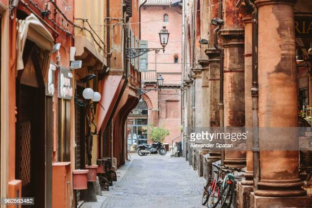 narrow cobbled street in the old town of bologna, italy - bologna stock pictures, royalty-free photos & images