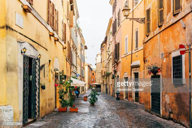 narrow cobbled street in trastevere neighborhood, rome, italy - italie photos et images de collection