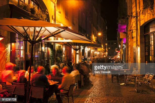 narrow cobbled street lined with people dining out in bordeaux - cultura francesa - fotografias e filmes do acervo