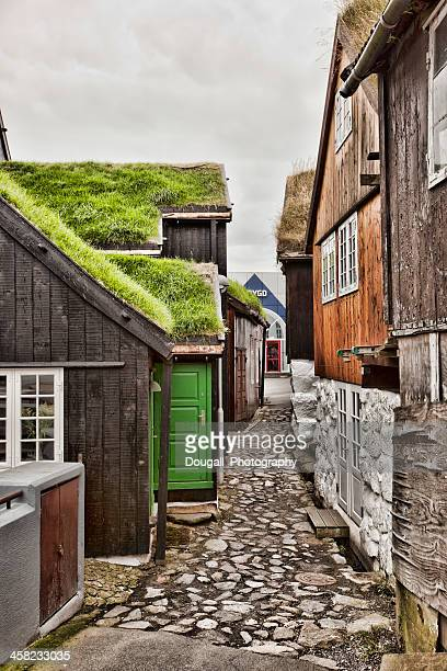 narrow cobblestone street with traditional torshavn houses - torshavn stock pictures, royalty-free photos & images