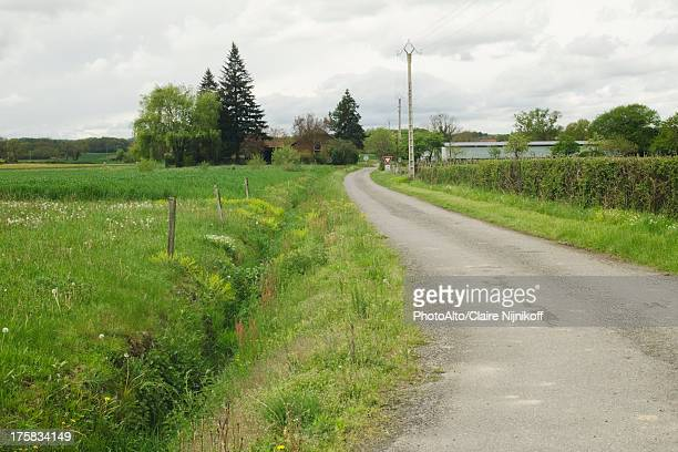 narrow country road leading to a village - ditch stock photos and pictures