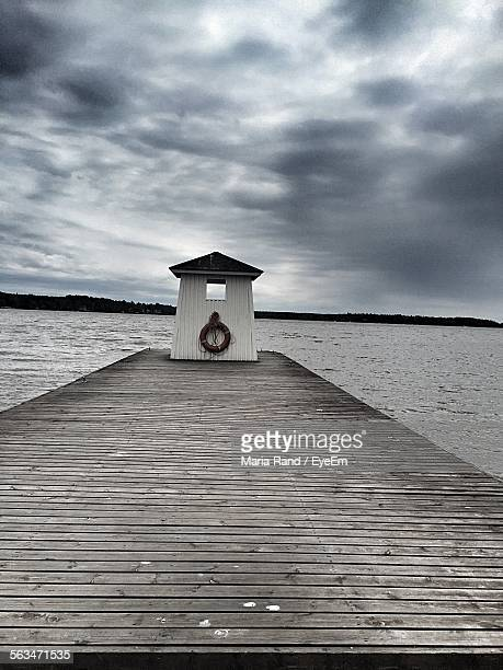 Narrow Jetty Leading To Calm Sea Against Clouds