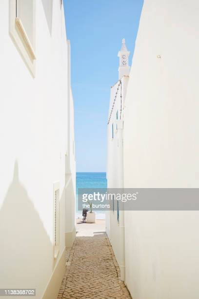 narrow passage between white painted houses to the sea - narrow stock pictures, royalty-free photos & images