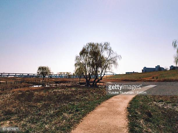 Narrow pathway along countryside landscape