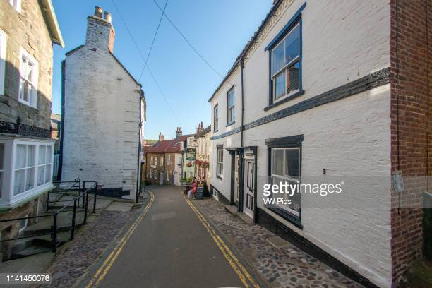 Narrow roadway leading through row houses in Robin Hoods Bay Yorkshire UK