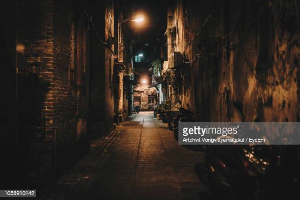 narrow street amidst buildings at night - alley stock pictures, royalty-free photos & images