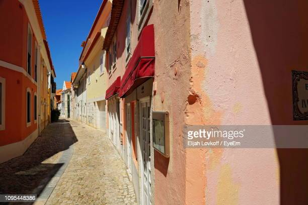 narrow street amidst buildings in town - cascais stock photos and pictures