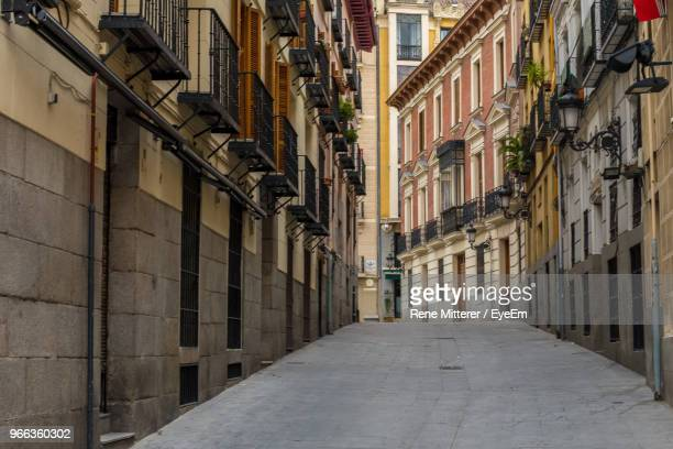 narrow street amidst buildings in town - madrid foto e immagini stock