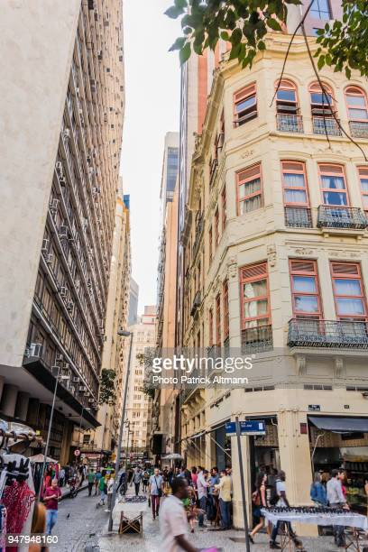 narrow street between buildings in busy commercial district downtown rio de janeiro at lunch time - latin america stock pictures, royalty-free photos & images