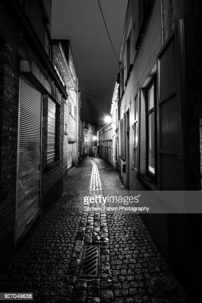 narrow street in a old town by night - samere fahim stock photos and pictures