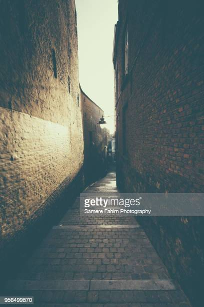 narrow street in a old town early morning - samere fahim stock photos and pictures
