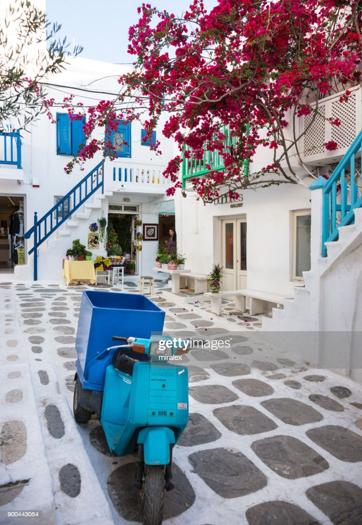 Narrow Street in Mykonos Town with Blue Motorbike and Bougainvillea Flowers : Stock Photo