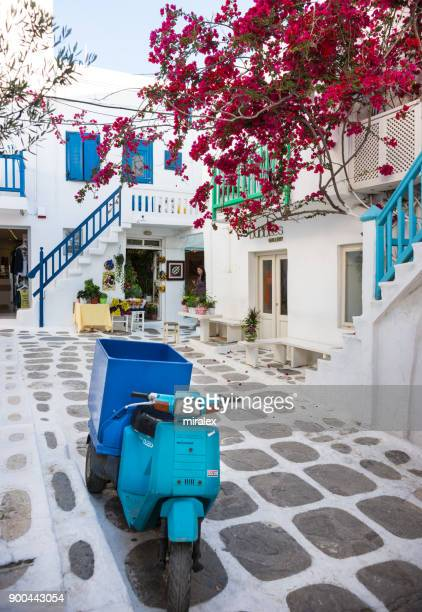 Narrow Street in Mykonos Town with Blue Motorbike and Bougainvillea Flowers