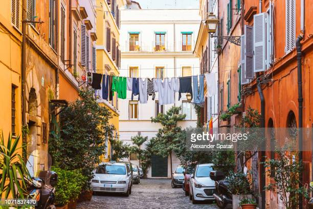 Narrow street in Trastevere with clean clothes on a washing line after laundry, Rome, Italy
