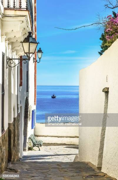 narrow street overlooking the sea in cadaques - cadaques stock pictures, royalty-free photos & images