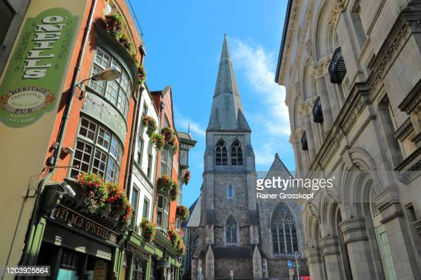 a narrow street with a pub facade decorated with flowers on the left leading to a big church - rainer grosskopf stock pictures, royalty-free photos & images