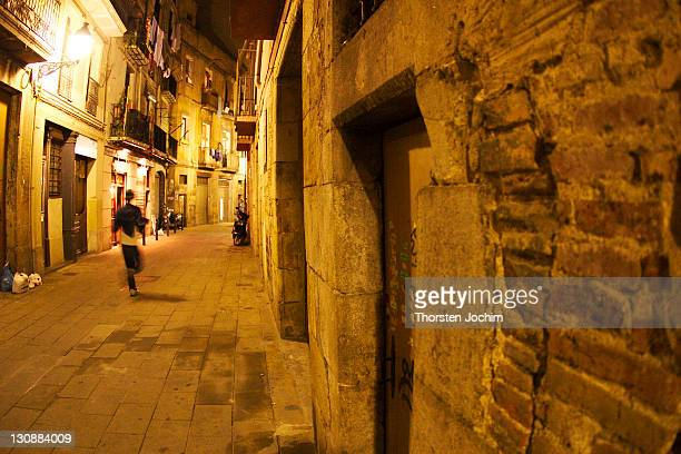 narrow streets and alleys of the old town in the nocturnal barcelona (spain), where a young man is passing quickly. - fuggire foto e immagini stock