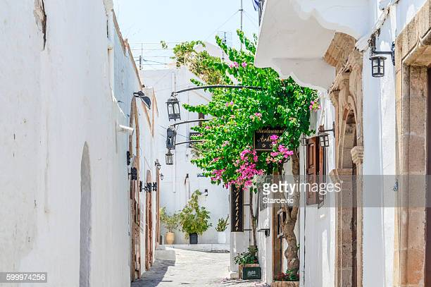 narrow streets and traditional architecture of lindos - rhodes, greece - lindos stock photos and pictures