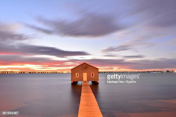 Narrow wooden jetty in calm sea at dusk