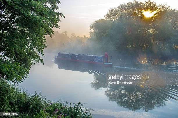 Narrowboat gently cruising up the Thames in the early morning mist and sunrise near Wallingford, Oxfordshire.