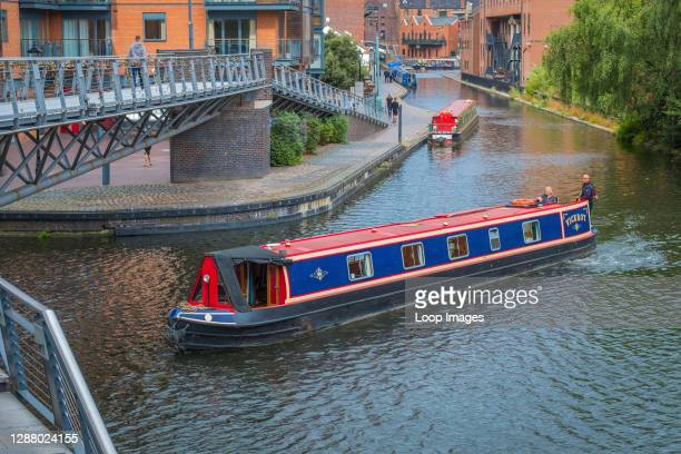 Narrowboat negotiates the corner on the Birmingham Canal Old Main Line at Salvage Turn Bridge by The Mailbox.
