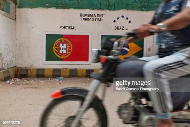 narrowed streets of lyari are painted with national flags of different countries playing fifa world cup 2018 - bandeira de portugal imagens e fotografias de stock