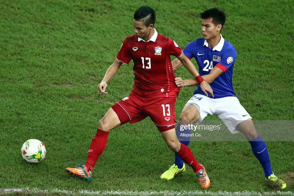 W. Narubaddin of Thailand is checked by Mohd Muslim of Malaysia during the 2014 AFF Suzuki Cup 2nd leg final match between Malaysia and Thailand at Bukit Jalil National Stadium on December 20, 2014 in Kuala Lumpur, Malaysia.