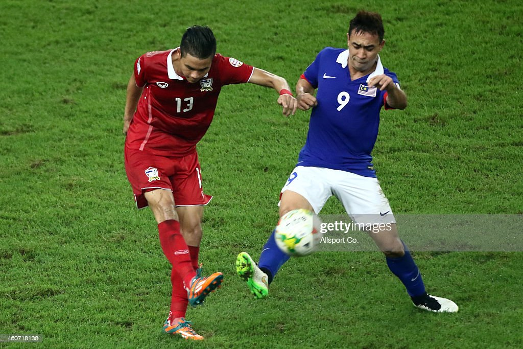 Narubadin of Thailand is checked by Norshahrul of Malaysia during the 2014 AFF Suzuki Cup 2nd leg final match between Malaysia and Thailand at Bukit Jalil National Stadium on December 20, 2014 in Kuala Lumpur, Malaysia.