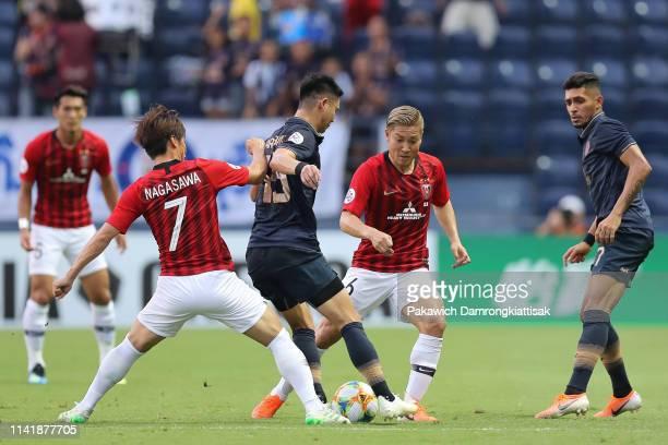 Narubadin Weerawatnodom of Buriram United controls the ball under pressure of Kazuki Nagasawa of Urawa Red Diamonds and Ryosuke Yamanaka of Urawa Red...