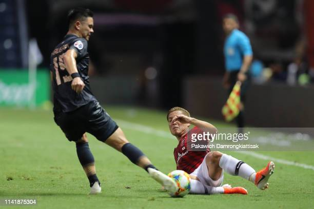 Narubadin Weerawatnodom of Buriram United is tackled by Ryosuke Yamanaka of Urawa Red Diamonds during the AFC Champions League Group G match between...