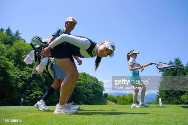 Naruha Miyata of Japan watches a photographer lying on the 14th tee during the second round of Daito Kentaku eHeyanet Ladies at Takino Country Club...