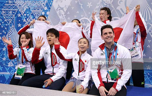 Narumi Takahashi and Kihara Ryuichi of Japan wait for their score with teammates and coaches during the Figure Skating Team Team Pairs Free Skating...