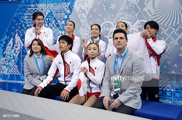 Narumi Takahashi and Ryuichi Kihara of Japan wait with teammates for their score after competing in the Figure Skating Pairs Short Program during the...