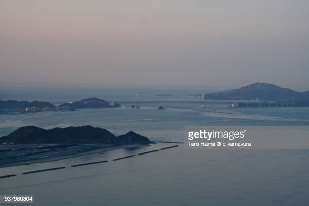 naruto strait between seto inland sea and pacific ocean, and onaruto bridge (great naruto bridge) on the strait in tokushima prefecture in japan sunset time aerial view from airplane - naruto stock photos and pictures