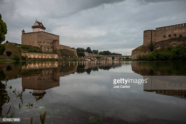 narva river at dusk separating russia and estonia - estonia stock photos and pictures