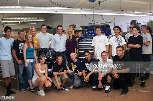 Nascar driver Jimmie Johnson center and wife Chandra pose with current shop class at his alma mater Granite Hills High School while promoting the...