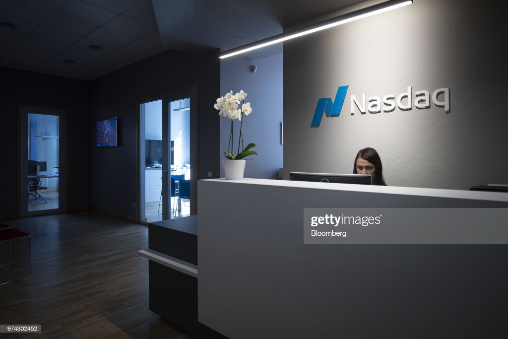 A Nasdaq Inc. logo sits illuminated behind a reception desk inside Riga Stock Exchange in Riga, Latvia, on Thursday, June 14, 2018. Latvia's plans to kick out risky cash from its scandal-plagued banks are about to accelerate. Photographer: Jasper Juinen/Bloomberg via Getty Images