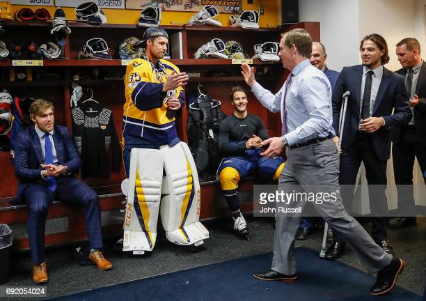 Nashville Predators assistant coach Phil Housley congratulates Pekka Rinne as First Star of the Game against the Pittsburgh Penguins during Game...