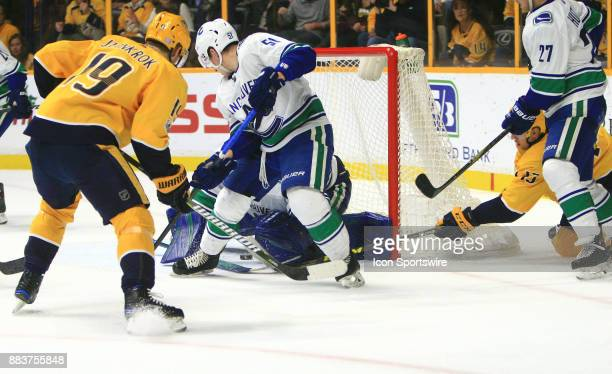 Nashville Predators center Nick Bonino pokes the puck beneath the pad of Vancouver Canucks goalie Anders Nilsson for a goal during the NHL game...