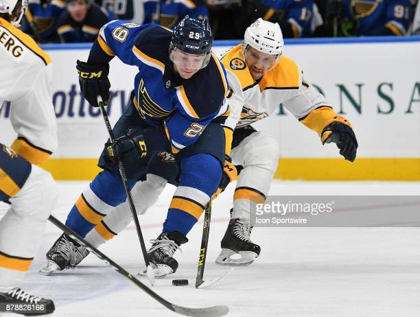 Nashville Predators center Nick Bonino tries to knock the puck away from St Louis Blues defenseman Vince Dunn during a NHL hockey game between the...