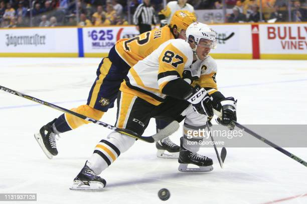 Nashville Predators center Ryan Johansen pokes the puck off the stick of Pittsburgh Penguins center Sidney Crosby during the NHL game between the...