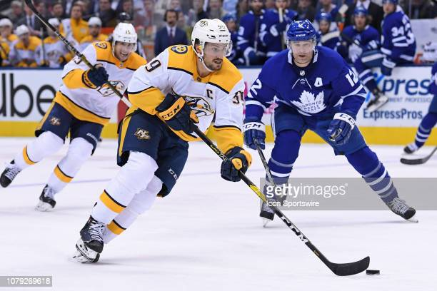 Nashville Predators Defenceman Roman Josi carries the puck in front of Toronto Maple Leafs Left Wing Patrick Marleau during the regular season NHL...